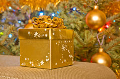 Golden Christmas gift next to a christmas tree Royalty Free Stock Photography