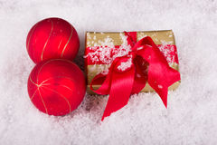 Golden Christmas gift with red Christmas balls in the snow Stock Photo