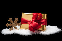 Golden christmas gift in snow.  Stock Image