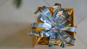 Golden christmas gift Under the Christmas Tree. Christmas gift box with nice ribbons. Close up stock footage