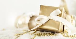 Golden Christmas giftbox. Closeup�golden giftbox�and balls decoration for Christmas Stock Images
