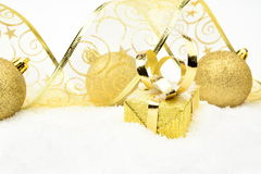 Golden christmas gifts,bauble ribbon on snow Stock Photography