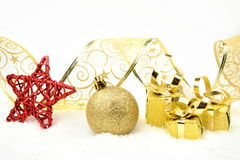 Golden christmas gifts,bauble ribbon on snow Stock Image