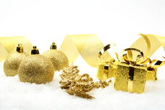 Golden christmas gifts,baubles golden ribbon on sno Stock Photo