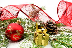 Golden christmas gifts,baubles with red ribbon and needles fir o Stock Images