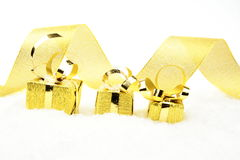 Golden christmas gifts in line with ribbon on snow Royalty Free Stock Photo