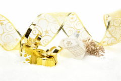 Golden christmas gifts, white bauble ribbon and rowan on snow Royalty Free Stock Image