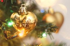 Golden Christmas heart hanging on the Christmas tree stock image