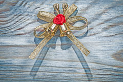 Golden Christmas knot with bell on wooden board holidays concept Stock Photography