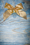 Golden Christmas knot on wooden board top view celebrations conc Royalty Free Stock Photo