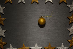Golden Christmas ornament on black slate background Stock Photography