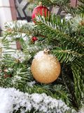 Golden christmas ornament on tree, snow, close up. Holiday, winter royalty free stock photo