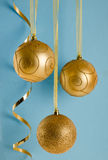 Golden Christmas Ornaments on blue background Royalty Free Stock Images