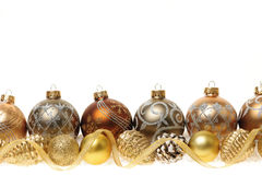 Golden Christmas ornaments border. Golden Christmas decorations with gold balls and ornaments on white background Stock Photos