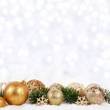 Golden Christmas ornaments and branches with twinkling background Royalty Free Stock Photo
