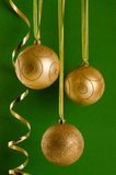 Golden Christmas Ornaments on green background Stock Photos