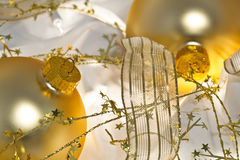 Golden Christmas Ornaments and Shiny Ribbon. Glowing golden Christmas ornaments with translucent ribbons, sparkling gold stars and twinkling white lights. Short royalty free stock photo