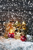 Golden christmas present, christmas ball, candle on pile of snow against wooden wall Stock Photos