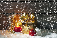 Golden christmas present, christmas ball, candle on pile of snow against wooden wall Royalty Free Stock Photo