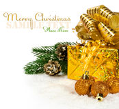 Golden Christmas presents and balls in the snow Stock Photo