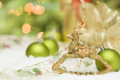 Golden Christmas Reindeer Ornament Among Snow, Bulbs and Ribbon Stock Photo