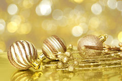 Golden Christmas scene. Gold Christmas scene with baubles and abstract light background royalty free stock images