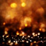 Golden Christmas shining glitter background with sparkling lig Stock Images