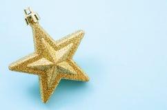Golden Christmas star. On blue background stock photos
