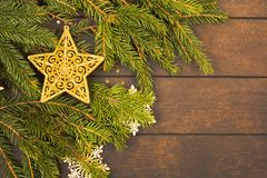 Golden christmas star decoration on fir tree branches with copy space. Golden christmas star decoration on fir tree branches over wooden background with copy stock image