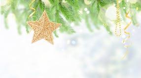 Golden christmas star. Hanging on christmas evergreen tree royalty free stock photo