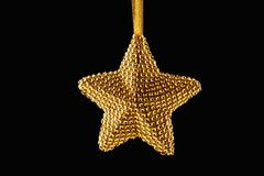 Golden Christmas star ornament on ribbon isolated on black background royalty free stock photo