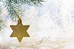 Golden Christmas star on a pine branch, beautiful blurred background. Copy space. Golden Christmas star on a pine branch, beautiful blurred background. Copy royalty free stock photo