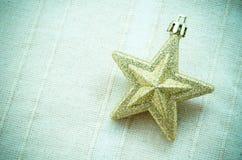 Golden Christmas star. Golden Christmas star on tablecloth stock photography