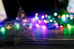 Golden christmas star toy on background of colorful garland ligh Royalty Free Stock Photo