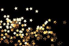 Golden Christmas stars. On black background royalty free stock image