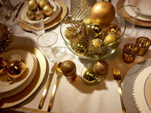 Golden Christmas table setting. And festive centrepiece Royalty Free Stock Photo