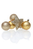 Golden christmas tree balls. Golden christmas tee balls and start on white background with reflection Royalty Free Stock Image