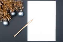 Creative decoration pattern with golden Christmas tree branches, silver baubles and pencil with copy space stock photos