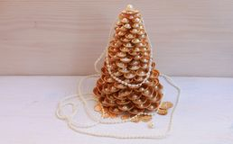 Golden Christmas Tree handmade from seashells on a white background stock image