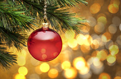 Golden Christmas Tree Scene Background. A red christmas ornament hanging from a tree with golden lighting with bokeh in the background. Please see my extensive