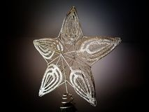 Golden Christmas tree star decoration. At the top of hte tree Royalty Free Stock Photography