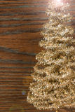 Golden christmas tree on a wooden background Stock Photos