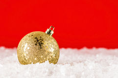 Golden chtistmas decoration. Golden Christmas decoration on artificial snow Royalty Free Stock Images