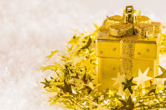 Golden chtistmas decoration. Golden Christmas decoration in tinsel on artificial snow Royalty Free Stock Photos