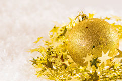 Golden chtistmas decoration. Golden Christmas decoration in tinsel on artificial snow Stock Images