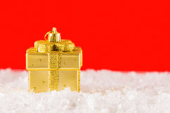 Golden chtistmas decoration. Present box shaped christmas decorations in artificial snow on red background Royalty Free Stock Image