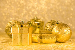 Golden chtistmas decorations. Present shaped Christmas decorations in front of Christmas ornaments Stock Photos