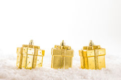 Golden chtistmas decorations. Three golden christmas decorations on artificial snow Royalty Free Stock Image