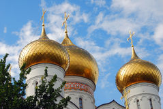 Golden church cupolas. Blue sky with clouds background. Royalty Free Stock Photo