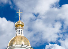 Golden church dome on cloudy sky background. Goldn dome of a St.Nicolas church in Saint-Petersburg with deep blue cloudy sky in a background stock image